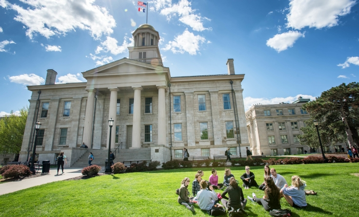 Students sit on the grass in front of the Old Capitol