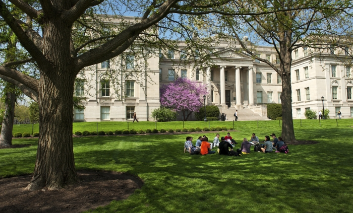 Students sitting in the grass on the Pentacrest.