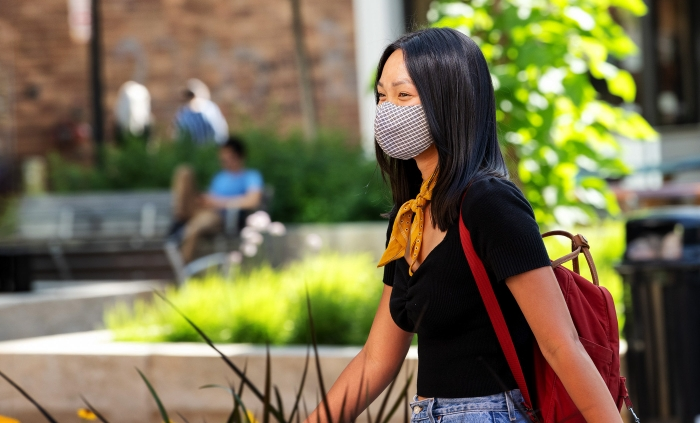 Student with face covering walking on campus.